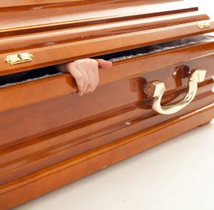 Mão de uma pessoa dentro do caixão (foto referencial)