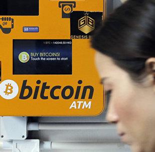 Mulher passa em frente a um caixa eletrônico de Bitcoins em Hong Kong, em 20 de dezembro de 2017.