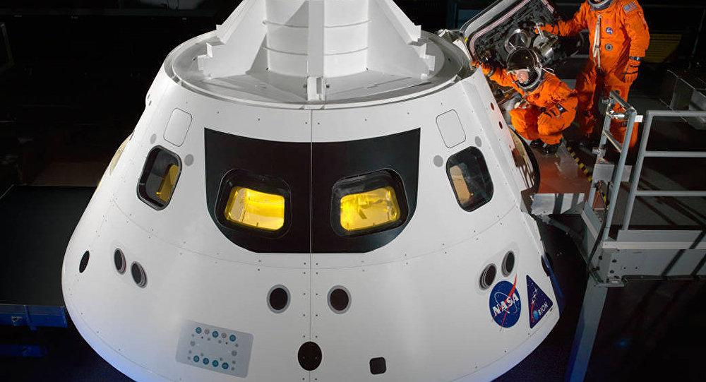 Astronautas da NASA, Cady Coleman e Ricky Arnold, entrando na nave espacial Orion