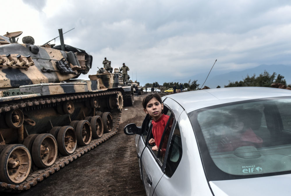 Menina turca observa como tanques e soldados do exército otomano se concentram perto da fronteira síria, na província de Hatay