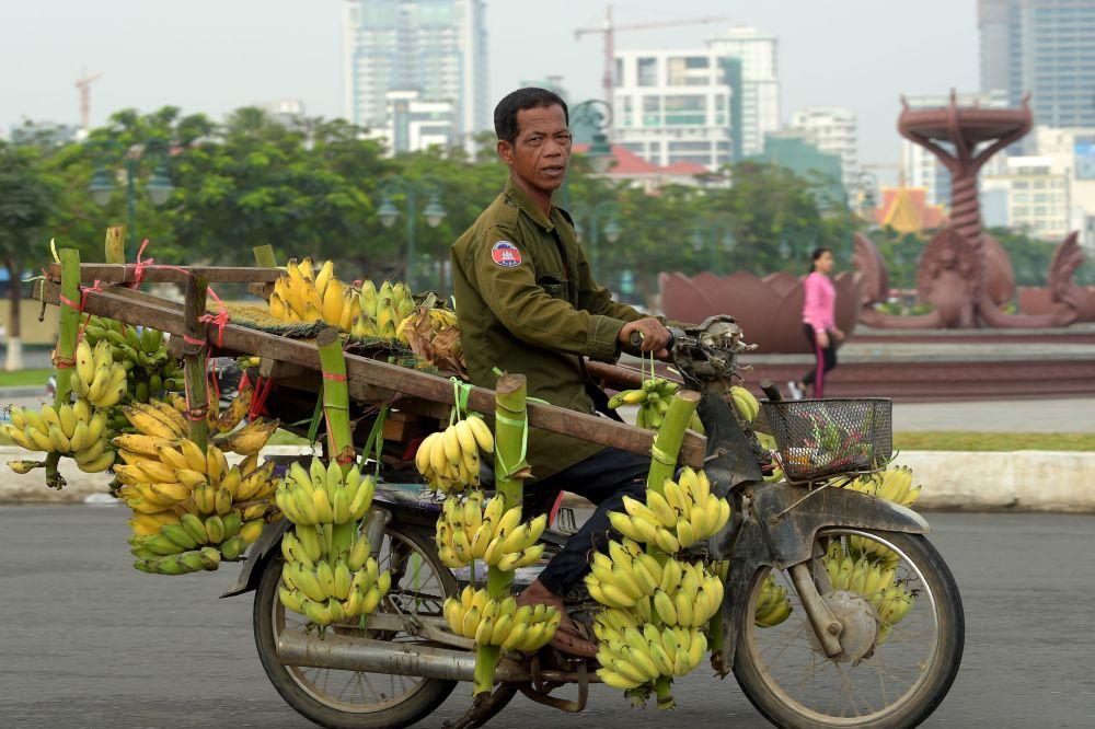 Cambojano carregado de bananas na cidade de Phnom Penh