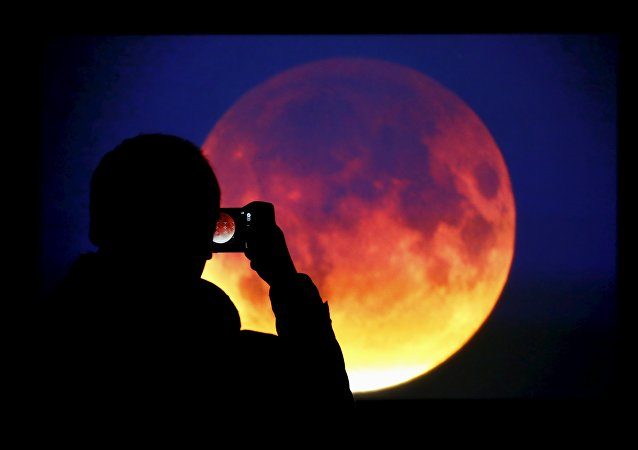 A man takes picture of the screen displaying the moon, appearing in a dim red colour, which is covered by the Earth's shadow during a total lunar eclipse in Warsaw, Poland September 28, 2015