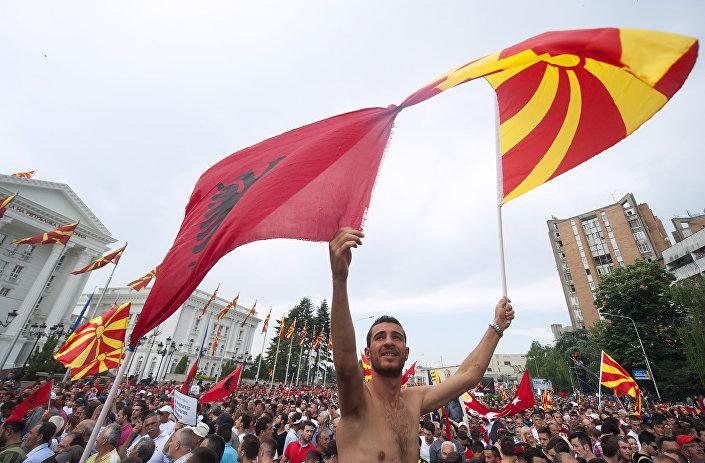 Manifestante com bandeiras da Macedônia (direta) e Albânia (esquerda) durante protesto contra o governo em Skopje, em 17 de maio de 2015.