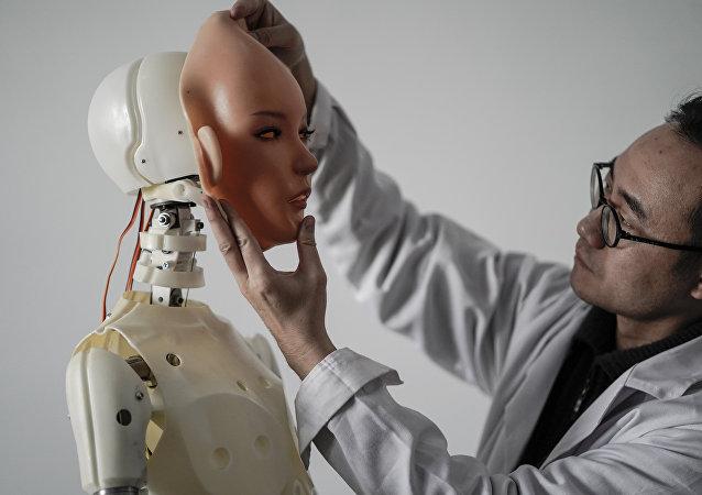 Engenheiro segurando um rosto de silicone diante de um robô na fábrica da EXDOLL