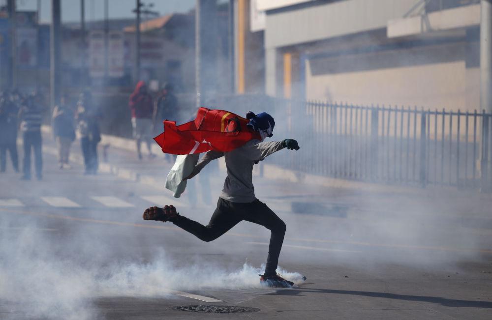 Manifestante dá pontapé em uma lata de gás enquanto a polícia impede apoiadores da oposição de se aproximarem do Estádio Nacional, onde decorre a posse do presidente hondurenho recém-eleito, Juan Orlando Hernandez, em Honduras