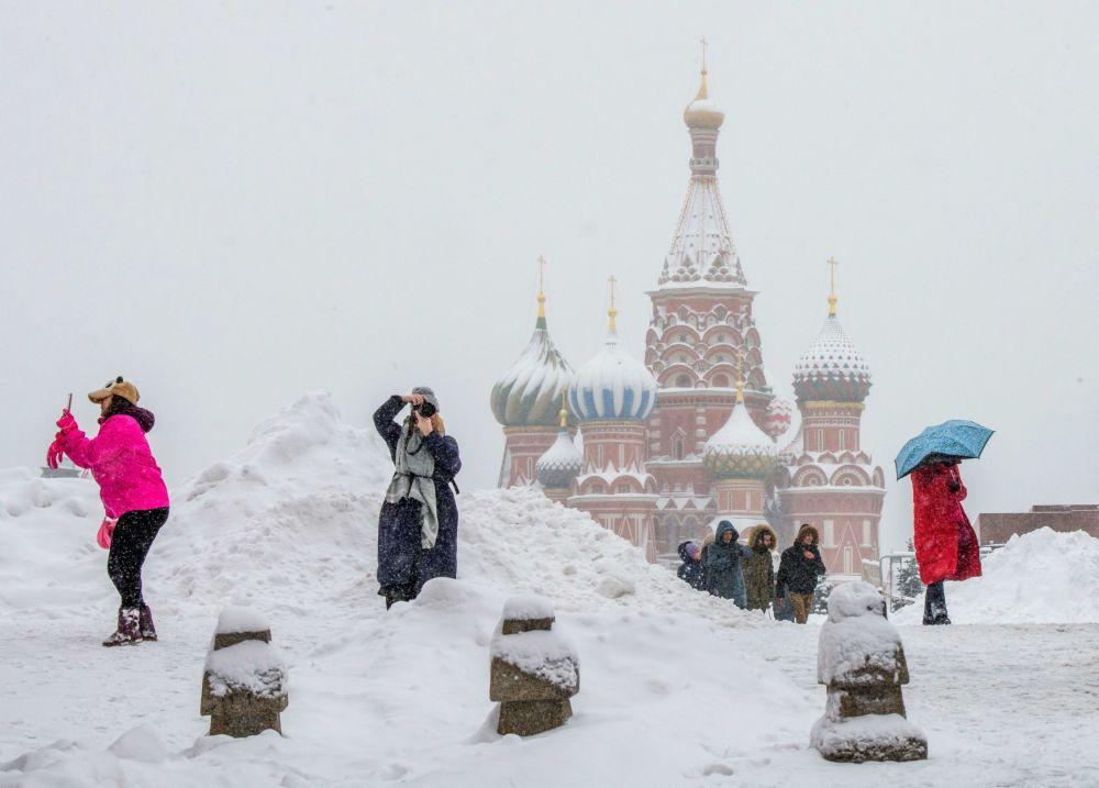 Turistas tiram fotos da Catedral de São Basílio em plena neve, na Praça Vermelha, em Moscou