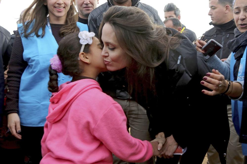 Enviada especial das Nações Unidas, a atriz Angelina Jolie, beija uma criança síria durante sua visita ao campo de refugiados Zaatari, na Jordânia