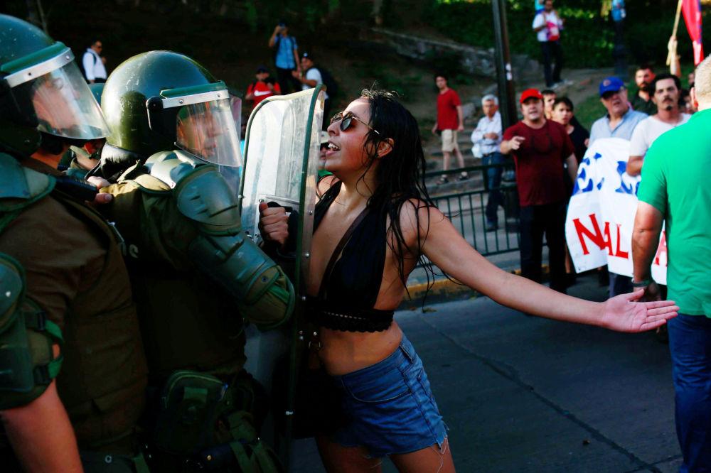 Manifestante confronta policiais durante uma ação popular em apoio à nacionalização das reservas de lítio do país, em Santiago, no Chile