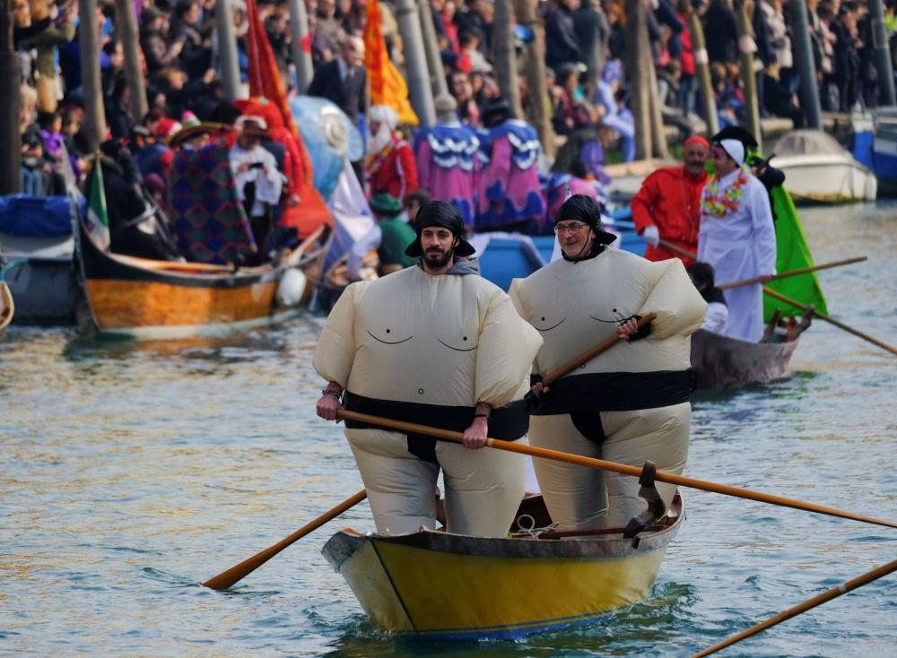 Residentes de Veneza participam da mascarada no Grande Canal no decorrer dos eventos festivos do Carnaval de Veneza, na Itália