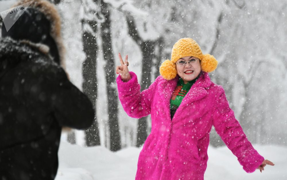 Jovem posa para foto durante nevada nas Colinas Vorobyovy, Moscou