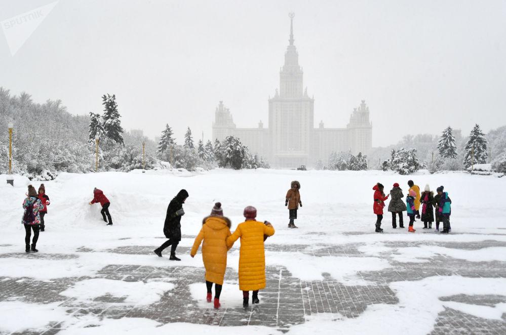 Turistas passeiam durante nevada na calçada em frente ao edifício da Universidade Estatal de Moscou, nas Colinas Vorobyovy