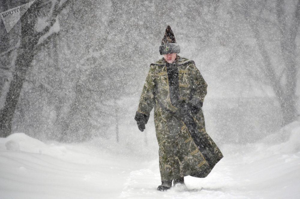 Homem vestido em traje tradicional russo passeia pelo museu-reserva Kolomenskoe, Moscou