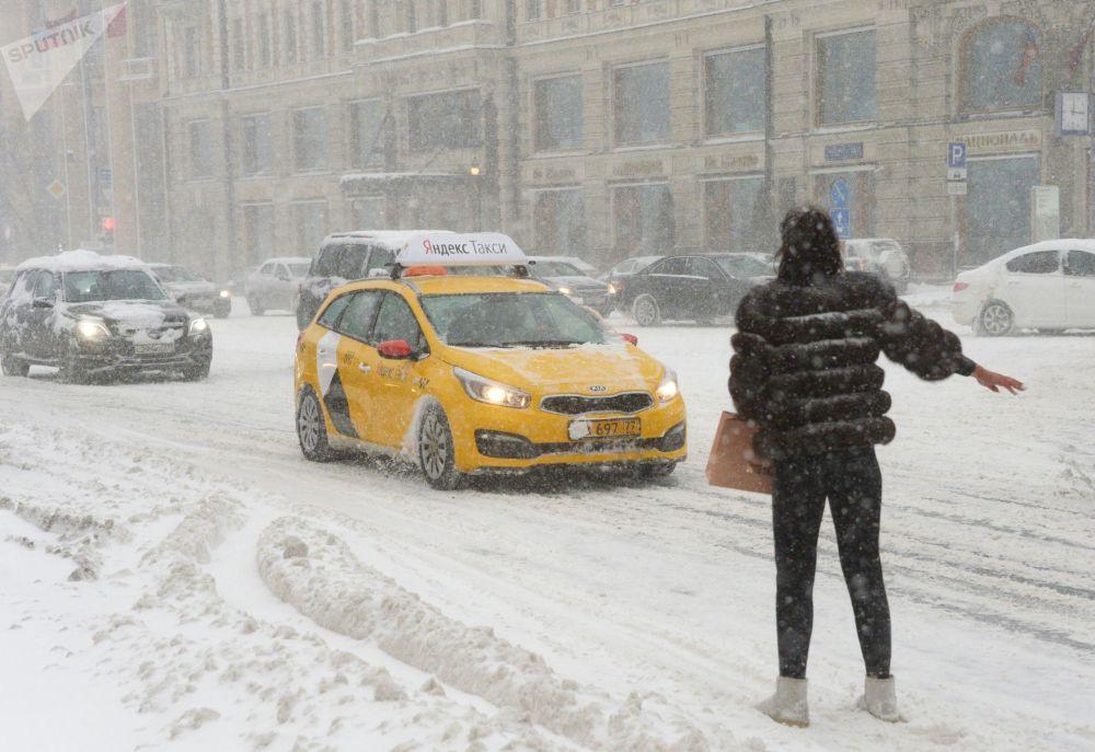 Jovem tenta pegar taxi durante nevada na rua Tverskaya – centro da cidade de Moscou