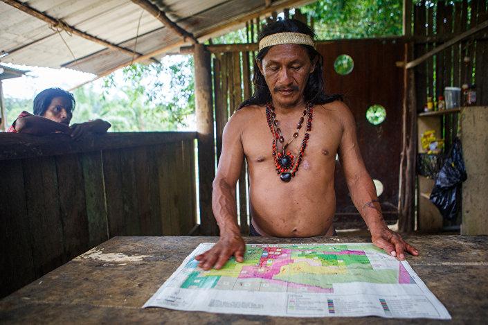 Um representante da etnia huaorani consulta mapa do território
