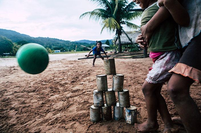Crianças jogando futebol em uma aldeia indígena