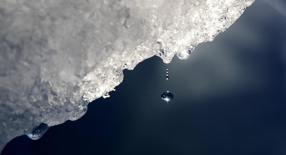 Uma gota de água caindo de um iceberg na Groenlândia