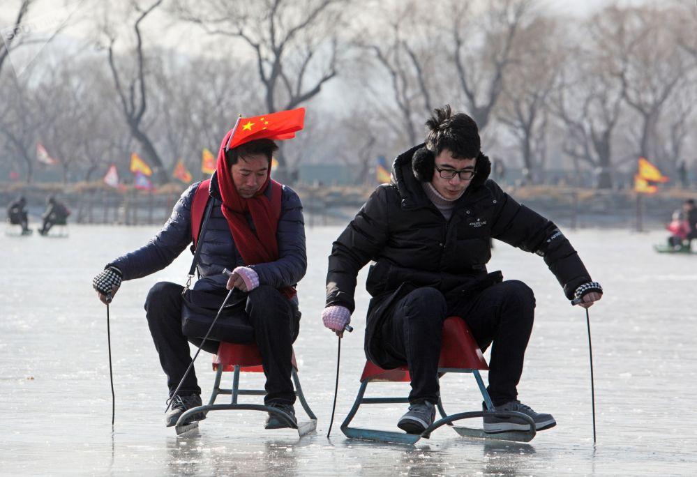 Turistas em trenó em lago chinês gelado nos arredores de Pequim