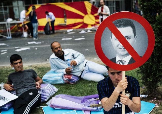 Um manifestante empunha o pequeno cartaz com uma foto de premeiro-ministro macedônio Nikola Gruevski durante o protesto antigovernamental no centro de Skopje no 17 de maio de 2015. Mais de 20.000 pessoas se reuniram na capital da Macedónia para exigir a renúncia do governo do primeiro-ministro Nikola Gruevski, que é responsavel pela crise política profunda e um surto de violência no país.