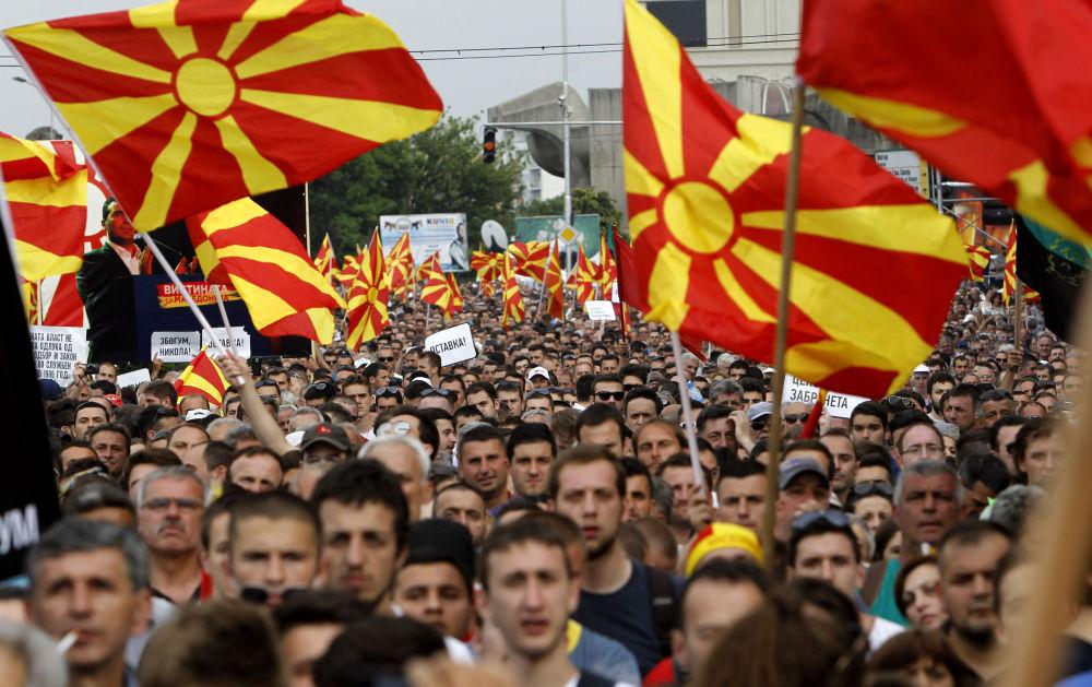 Os manifestantes estão carregando bandeiras macedônias e albanesas gritando Adeus Nikola! em frente do prédio do governo em Skopje, Macedónia. A oposição de Macedônia reuniu se nas ruas protestando contra o governo e exigindo a renúncia do primeiro-ministro Nikola Gruevski.