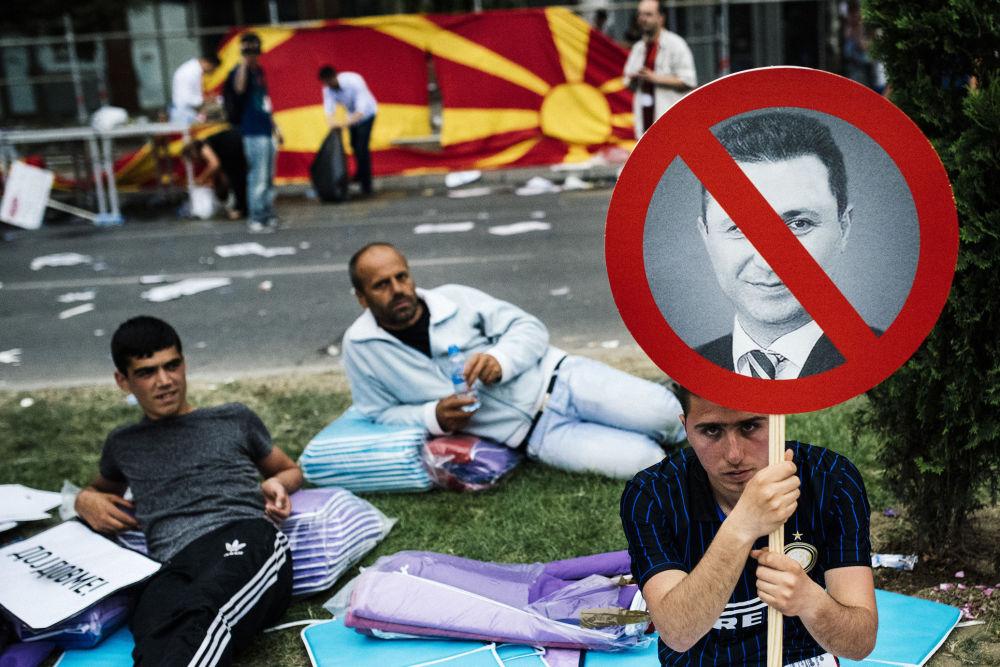 Protestos na Macedônia. Um manifestante empunha o pequeno cartaz com uma foto de premeiro-ministro macedônio Nikola Gruevski durante o protesto antigovernamental no centro de Skopje no 17 de maio de 2015. Mais de 20.000 pessoas se reuniram na capital da Macedónia para exigir a renúncia do governo do primeiro-ministro Nikola Gruevski, que é responsavel pela crise política profunda e um surto de violência no país.