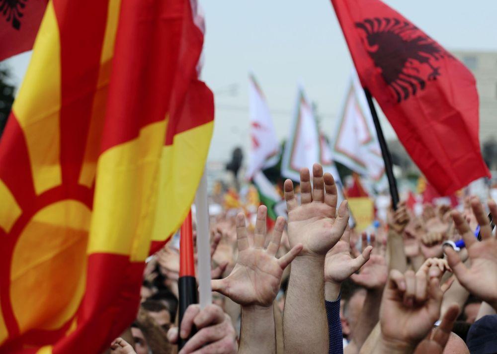 Os manifestantes estão carregando bandeiras macedônias e albanesas durante o protesto antigovernamental.