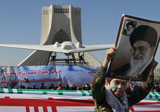 Menino mostra um cartaz do líder supremo do Irã, aiatolá Ali khamenei, enquanto passa perto do drone estadunidense RQ-170 Sentinel