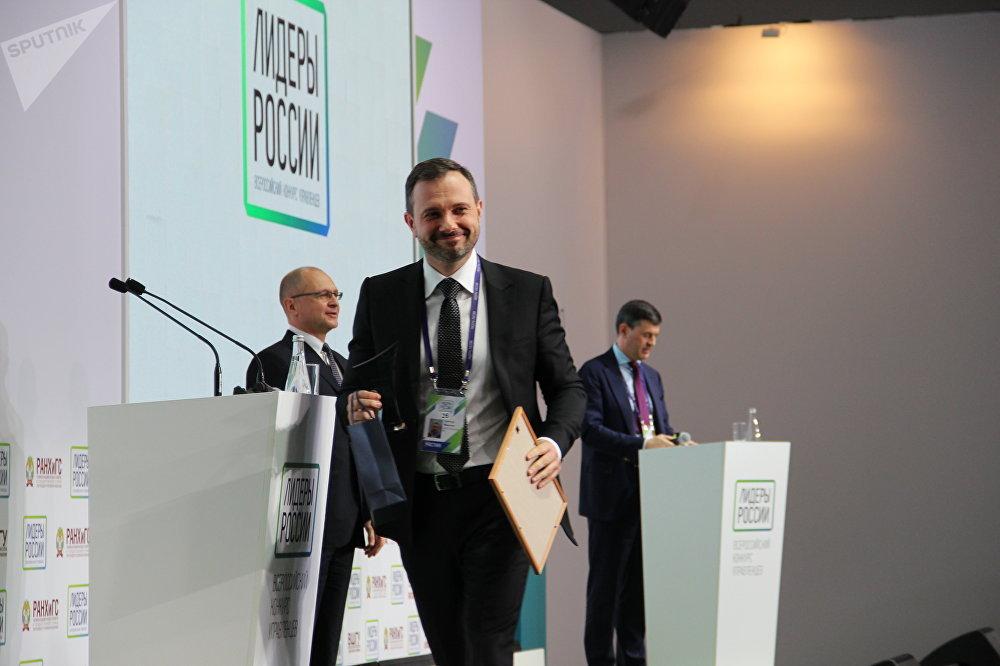 Maksim Karpov, funcionário da NLF Group, sorri após receber o certificado de vencedor do concurso Líderes da Rússia