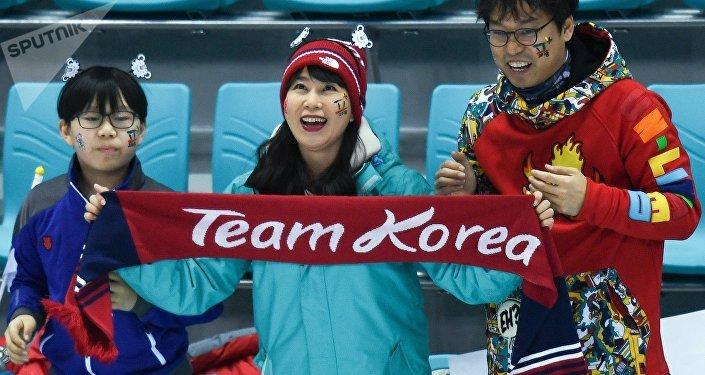 Torcedores apoiam a seleção conjunta de hóquei no gelo formada por jogadoras norte e sul-coreanas nos Jogos Olímpicos de 2018