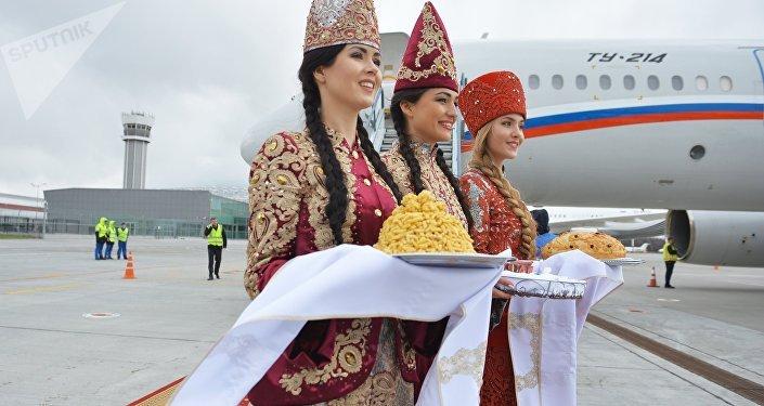 Moças em trajes nacionais dão boas-vindas ao presidente Putin no aeroporto de Kazan, foto de arquivo