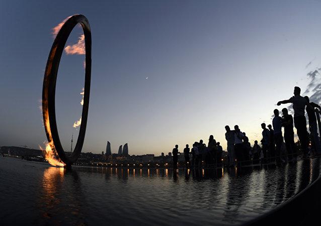 Pessoas olhando para instalação de fogo no litoral do mar Cáspio em Baku