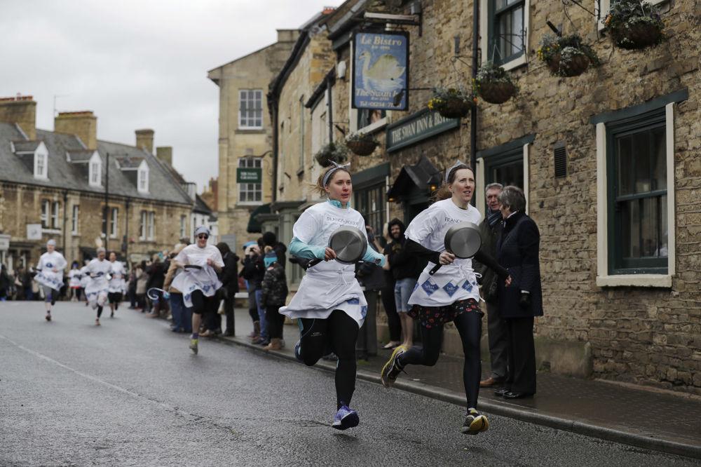 Participantes de uma corrida de panquecas nas vésperas do Jejum, no Reino Unido