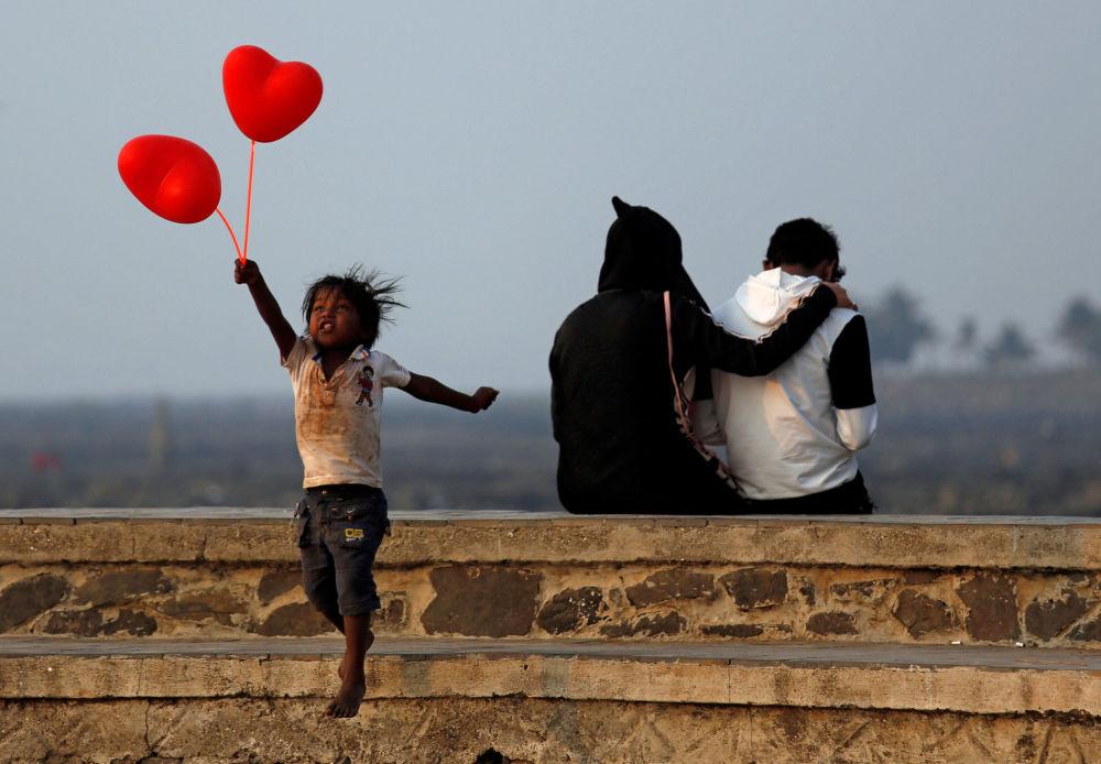 Criança com balões de ar em forma de coração no Dia dos Namorados, na Índia