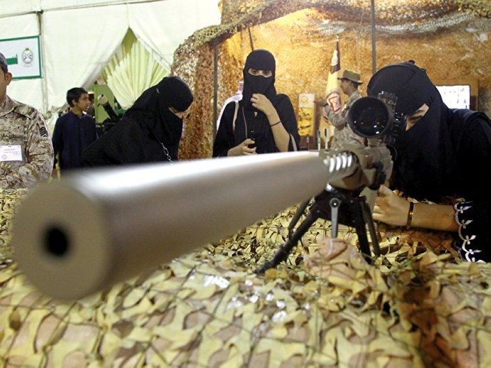 Mulher verifica arma exibida no evento dedicado à celebração da classificação de Abha como capital do turismo árabe, 20 de abril de 2017