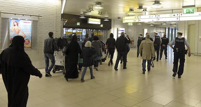 Policiais escoltam um grupo de refugiados após a chegada ao aeroporto de Hanôver, no centro da Alemanha, em 4 de abril de 2016.