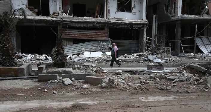 Civil caminha por rua destruída de Haza, na região síria de Ghouta Oriental, perto de Damasco