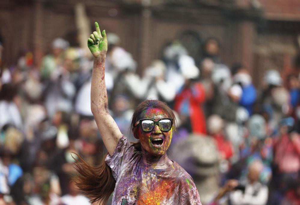 Turista durante comemoração do tradicional festival Holi em Katmandu, Nepal