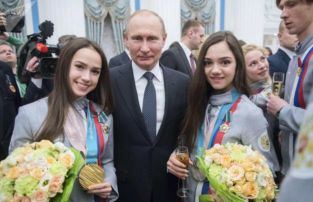 Vladimir Putin e as medalhistas de patinação artística nas Olimpíadas de Inverno de PyeongChang, Alina Zagitova (à esquerda) e Yevgenia Medvedeva (à direita), em fevereiro de 2018