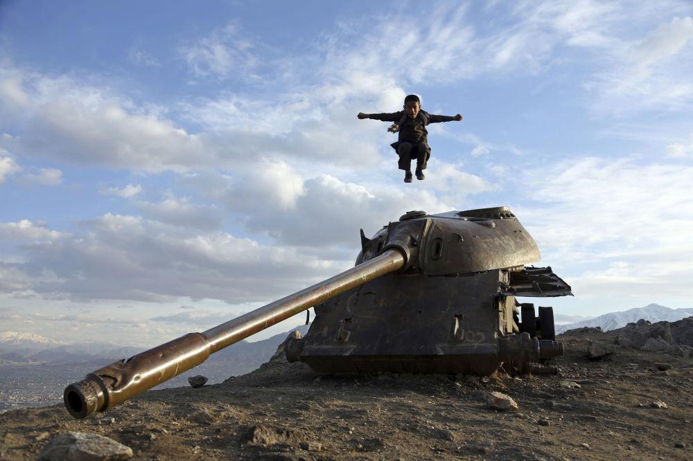 Menino afegão salta da torre de um tanque nos arredores de Cabul
