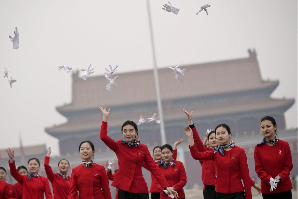 Moças da equipe de hospitalidade atiram as luvas durante o Congresso Nacional do Povo, na Praça Tiananmen em Pequim, China