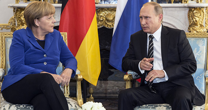 German Chancellor Angela Merkel, left, discusses with Russian President Vladimir Putin during a bilateral prior to a summit on Ukraine at the Elysee Palace in Paris, France