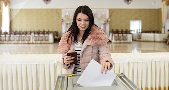 Jovem depositando seu voto nas eleições presidenciais da Rússia 2018, 18 de março 2018