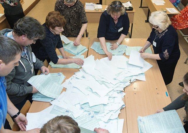 Membros da comissão eleitoral local durante contagem de votos na cidade russa de Petropavlovsk-Kamchatsky, onde as primeiras seções da Rússia já foram fechadas