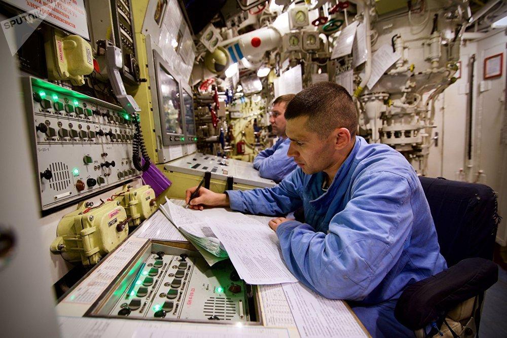 Membro da tripulação do submarino perto do painel de controle de armas