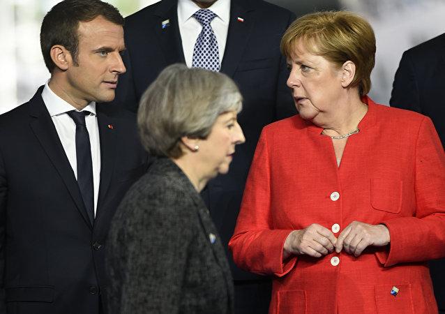 Primeira ministra britânica, Theresa May (centro), passa em frente da chanceler alemã, Angela Merkel (direita), e de Emmanuel Macron (esquerda), presidente da França.