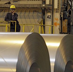 Um trabalhador olha por detrás de rolos de aço em Ohio, nos EUA, enquanto o secretário norte-americano do Trabalho, Seth Harris, discursa.