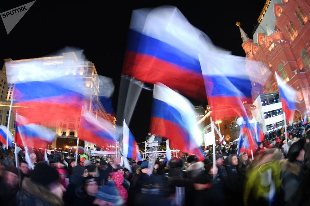 Participantes da manifestação dedicada ao quarto aniversário da reunificação da Crimeia com a Rússia, Moscou.