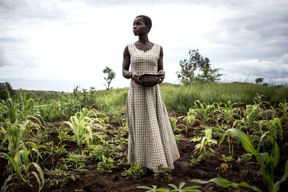 Uma mulher planta sementes no acampamento improvisado para deslocados internos na República Democrática do Congo.