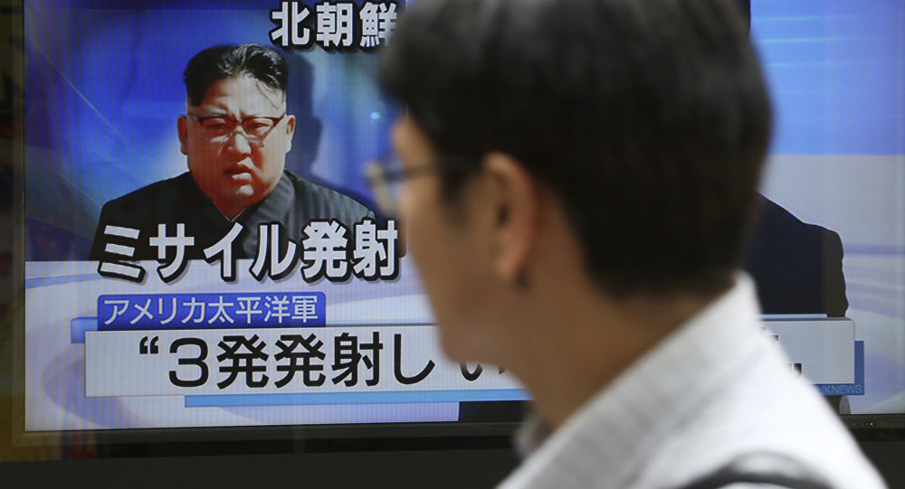 Passers-by watch a TV news program showing image of North Korean leader Kim Jong Un, in Tokyo, Saturday, Aug. 26, 2017