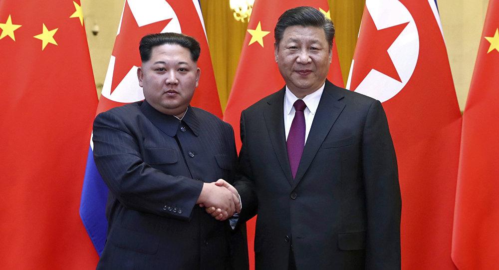 Kim Jong-un (à esquerda) e Xi Jinping (à direita) apertam as mãos durante a vista do líder norte-coreano à China.
