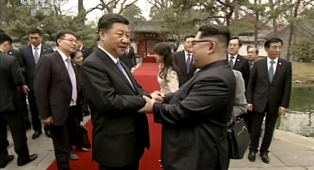 Os líderes norte-coreano, Kim Jong-un, e chinês, Xi Jinping, saúdam um ao outro durante encontro não oficial em Pequim em 25 de março de 2018